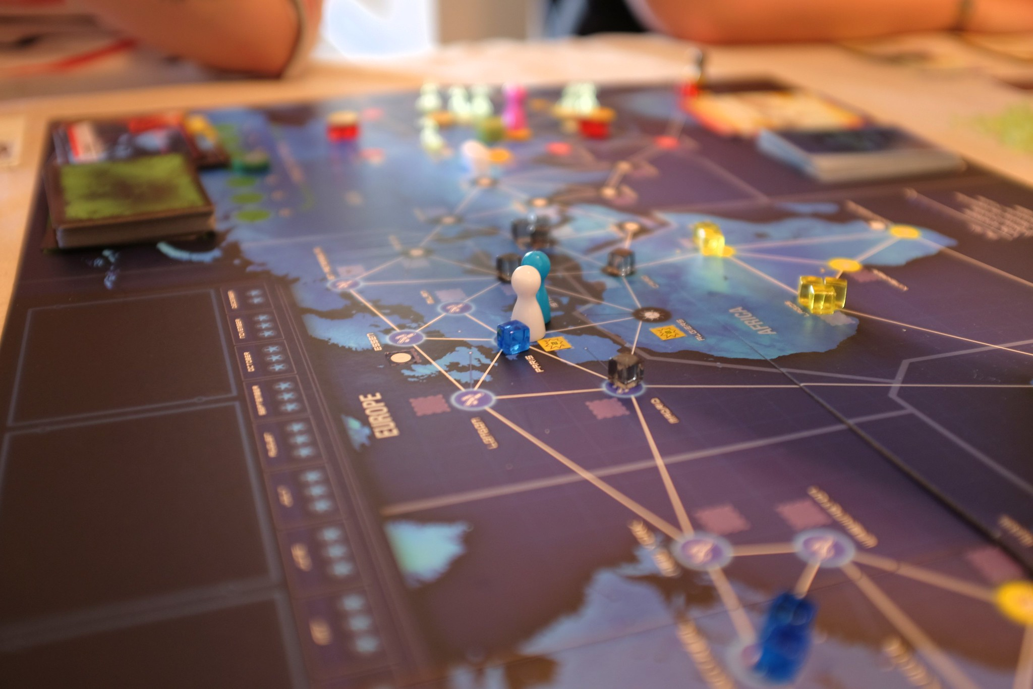 Close up of the board game Pandemic: Legacy - a cooperative game about trying to battle disease, emulating some of the ways people play to understand epidemics like the impact of coronavirus.